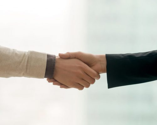 Businessman and businesswoman handshaking, close up of male and female hands shaking, successful deal and partnership, business partners making agreement, forming strong working relations, copy space